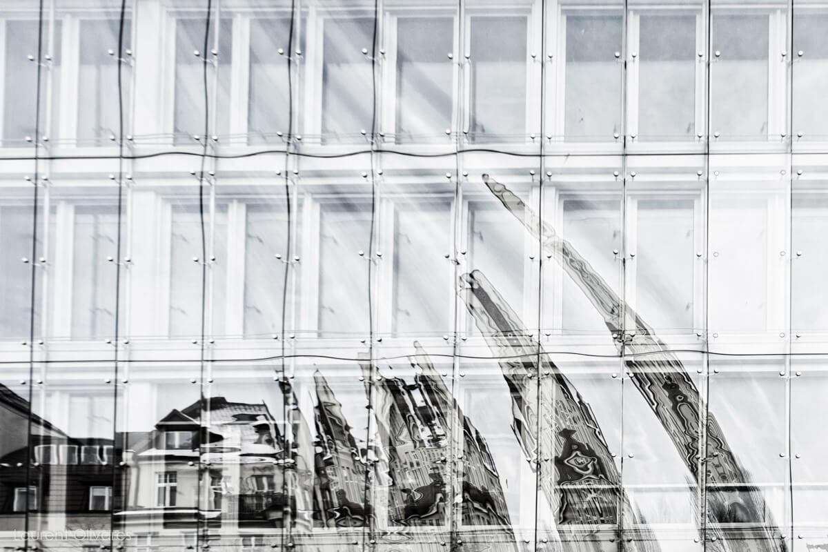 Un reflet de bâtiments sur des vitres ondulées